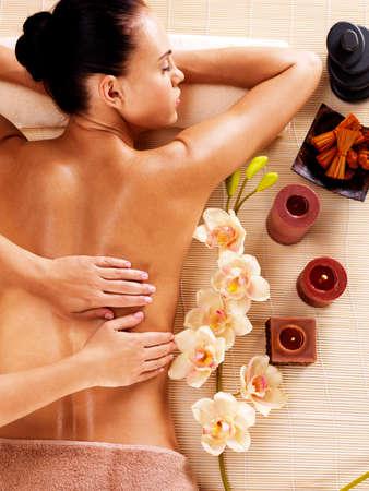Masajista haciendo masaje en la espalda de la mujer en el salón del balneario