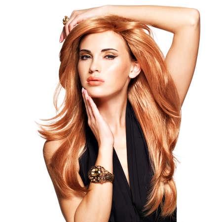 cabello negro: Mujer hermosa con el pelo largo roja directa en un vestido negro que toca su cara. Modelo de moda en estudio. Aislado en blanco Foto de archivo
