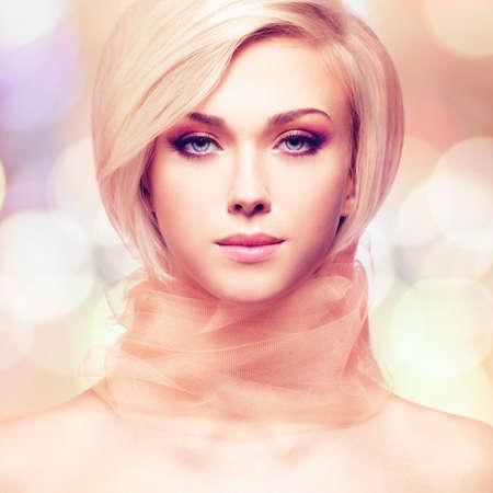 mujer elegante: Mujer joven hermosa con la tela rosada que presenta en estudio en el fondo creativo.
