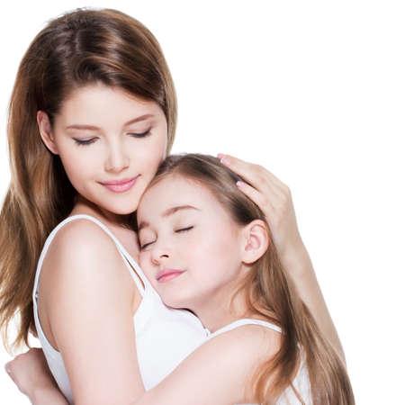 mama e hija: Madre joven hermosa con una pequeña hija de 8 años se abrazan en el estudio