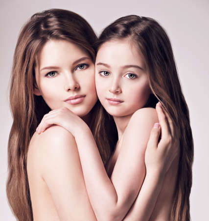 nude little girls: Beautiful naked mother and small daughter 8 years with long brown hair embrace each other at studio Stock Photo