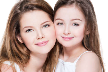 8 years: Beautiful and happy young mother with a small daughter 8 years embrace each other at studio Stock Photo
