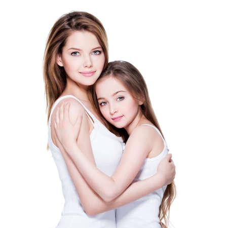madre e hija: Madre joven hermosa con una pequeña hija de 8 años se abrazan en el estudio