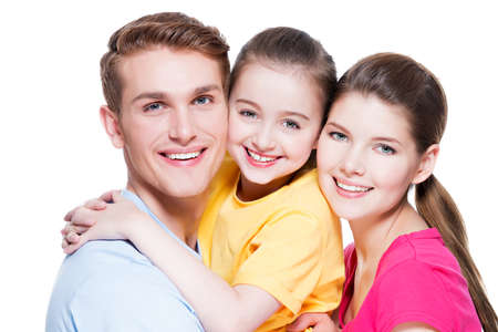 Portrait of happy smiling young family with kid in colored shirts looking at camera - isolated on white. Stock Photo