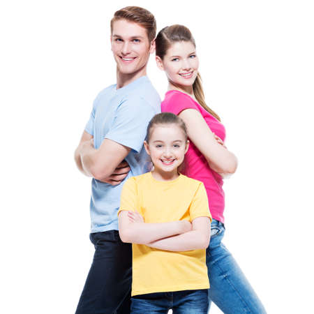 white back: Happy attractive family with daughter standing back to back at studio - isolated on white. Stock Photo
