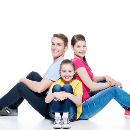 aucasian: Happy young family with kid sitting on the floor at studio - isolated on white.