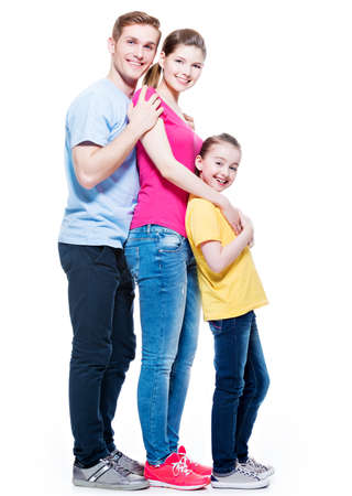 family isolated: Full portrait of the happy young family with daughter in multicolor shirts - isolated on white background. Stock Photo