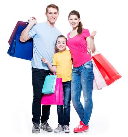 chicas de compras: Familia feliz con bolsas de la compra de pie en el estudio sobre fondo blanco.
