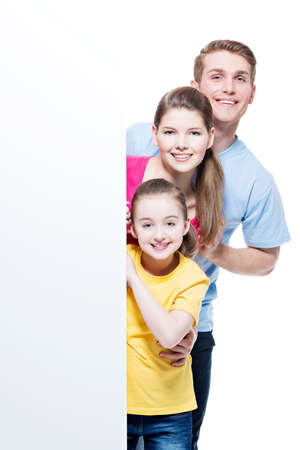 a young family: Portrait of happy young smiling family with  banner - isolated on a white background.