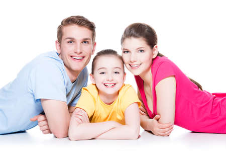 aucasian: Portrait of happy smiling family with kid sitting in colorful shirt lying on the floor at studio - isolated on white.