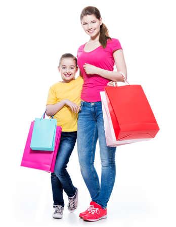 mama e hija: Feliz madre e hija sonriente con bolsas de compras - aislados sobre fondo blanco. Foto de archivo