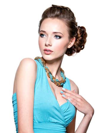 보석 가진 젊은 아름 다운 여자. 소녀 bijouterie 입고 파란색 드레스 패션입니다. 예쁜 모델 흰색 배경 위에 포즈