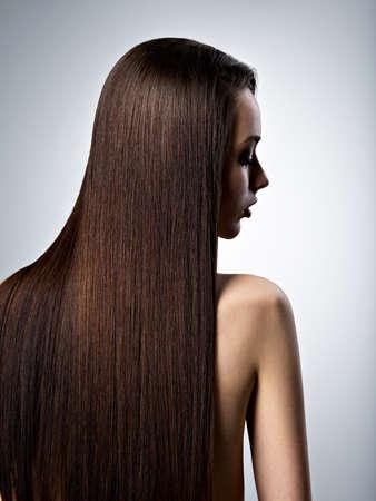 Retrato de la hermosa mujer con cabello castaño largo recto en el estudio