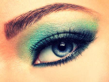 maquillaje de ojos: Ojo de la mujer con los ojos verdes del maquillaje. Pestañas largas