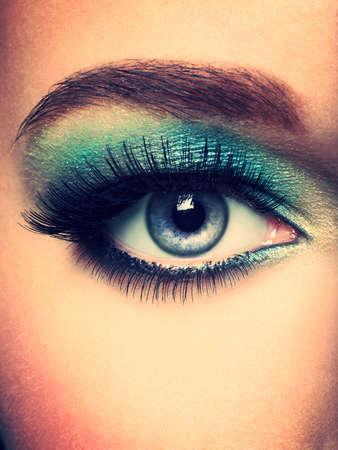 motton: Womans eye with green eye make-up. Long eyelashes
