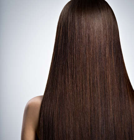Rear Portrait of  woman with long brown straight  hair at studio