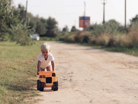 trundle: Adorable little blond boy playing with big yellow car outdoors. Stock Photo
