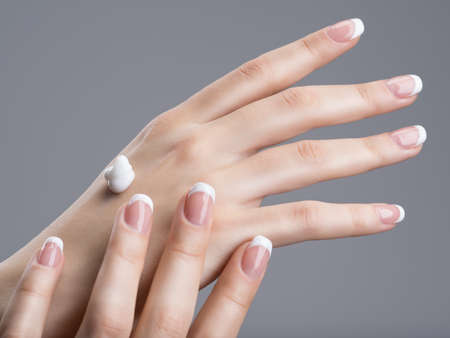 Close-up female hands apllying hand cream.  with french manicure on nails 스톡 콘텐츠