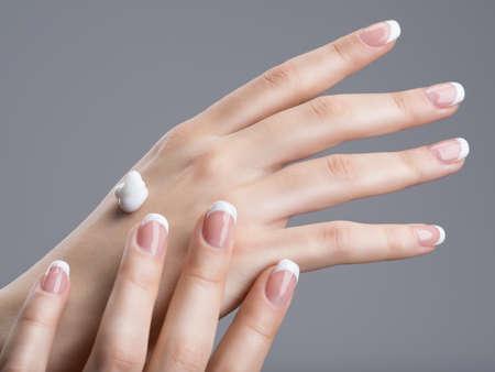 Close-up femminile mani applicando crema per la mano. Con manicure francese sulle unghie Archivio Fotografico - 54100867