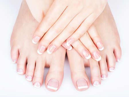 manos y pies: Foto del primer de una hembra blanca con pies de pedicura francés en las uñas. en el salón de spa. concepto de cuidado de las piernas Foto de archivo