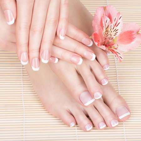 manicure and pedicure: Closeup photo of a female feet at spa salon on pedicure and manicure procedure - Soft focus image