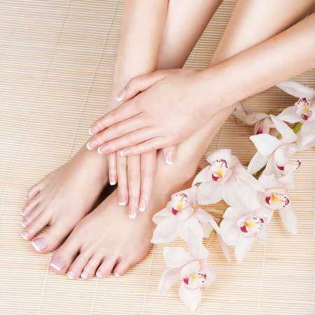 manicura: Closeup photo of a female feet at spa salon on pedicure and manicure procedure - Soft focus image
