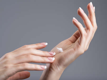 Close-up female hands apllying hand cream.  with french manicure on nails Stock Photo