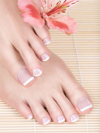 french pedicure: Closeup photo of a female feet with white french pedicure on nails. at spa salon. Legs care concept