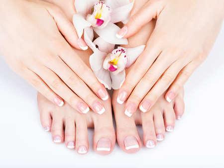 Foto del primer de un pies femeninos en el salón de spa en pedicura y manicura procedimiento - La imagen del foco suave