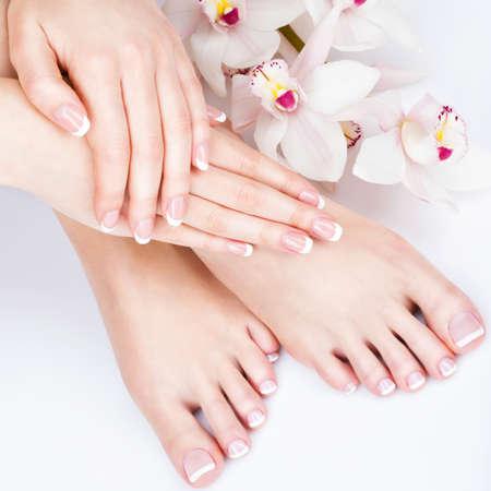 Foto del primer de un pies femeninos en el salón de spa en pedicura y manicura procedimiento - La imagen del foco suave Foto de archivo