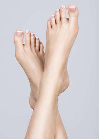 Detailním fotografie ženské nohy s bílou francouzská pedikúra na nehtech. v lázních salonu. Koncepce péče o nohy