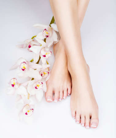 french: Closeup photo of a female feet with white french pedicure on nails. at spa salon. Legs care concept