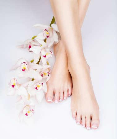 Foto do close up do pés fêmeas com pedicure francês branco nas unhas. no salão spa. Conceito de cuidados de pernas