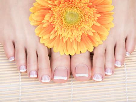 Foto del primer de una hembra blanca con pies de pedicura francés en las uñas. en el salón de spa. concepto de cuidado de las piernas