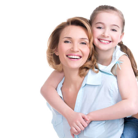 toothy smiles: CLoseup portrait of happy  white mother and young daughter - isolated. Happy family people concept.