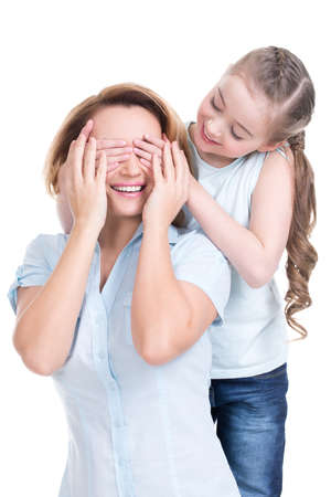 closes eyes: Young daughter closes hands eyes mom - isolated. Happy family people concept.