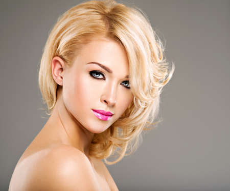 nude blonde girl: Beautiful woman with long blond curly hair. Portrait of fashion model with bright makeup.