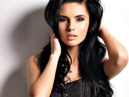 Schöne reizvolle junge Frau, brünett mit langen Haaren. Portrait einer hübschen Mode Modell posiert im Studio. Standard-Bild
