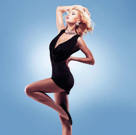 nude blonde girl: Beautiful sexy woman  in black dress  posing elegant at studio Stock Photo