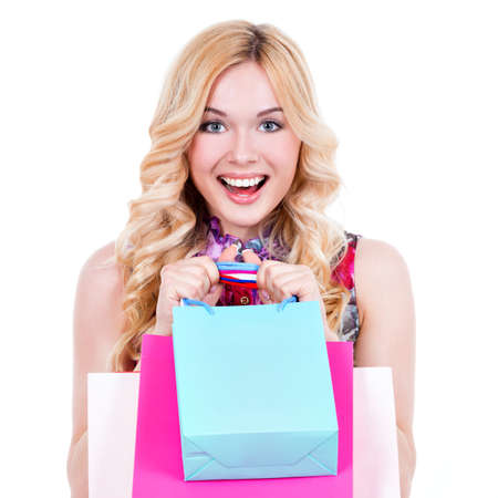 Happy young blonde woman with colored shopping bags in pink dress over white background. photo