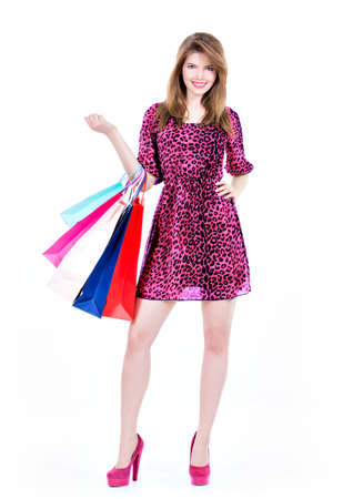 Portrait of beautiful happy woman with multicolor shopping bags in dress - isolated on a white background. photo