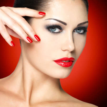 Beautiful woman with red nails and fashion makeup photo