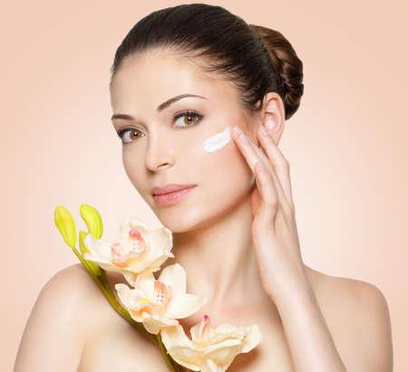 piel humana: Mujer joven con crema cosmética en una cara limpia y fresca. concepto de estilo de vida saludable
