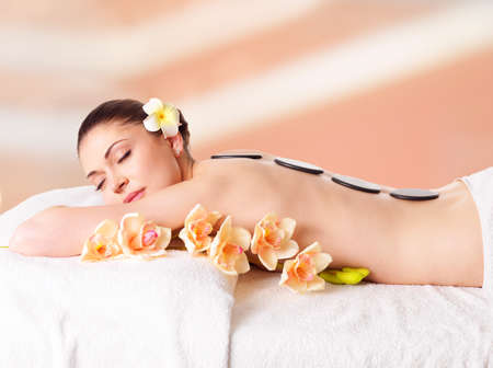 Adult beautiful woman relaxing in spa salon with hot stones on back