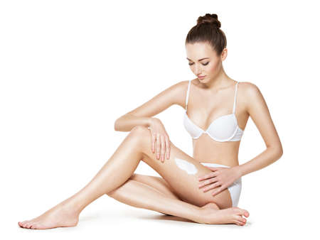 hair and beauty: beautiful young woman depilating her legs by waxing -  studio on white background Stock Photo