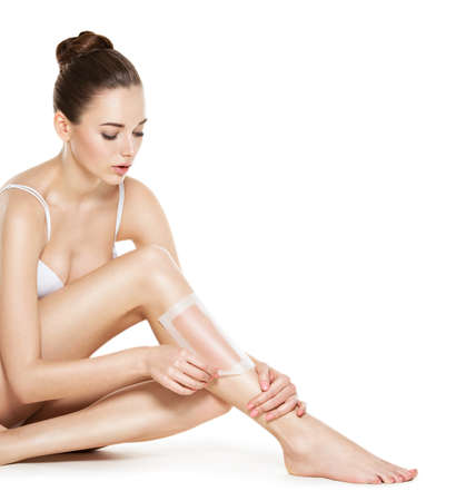 depilate: beautiful young woman depilating her legs by waxing -  studio on white background Stock Photo