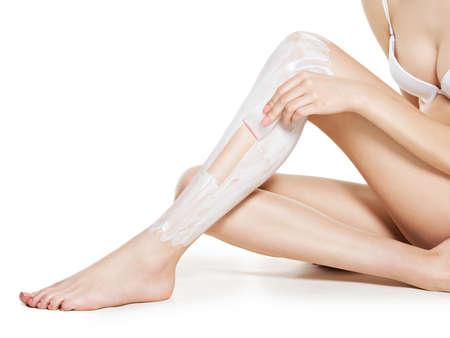 depilate: woman depilating her legs by waxing -  studio on white background