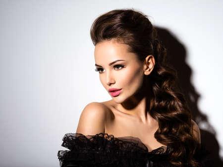 Beau visage d'une jeune fille sexy en robe noire posant au studio sur fond blanc