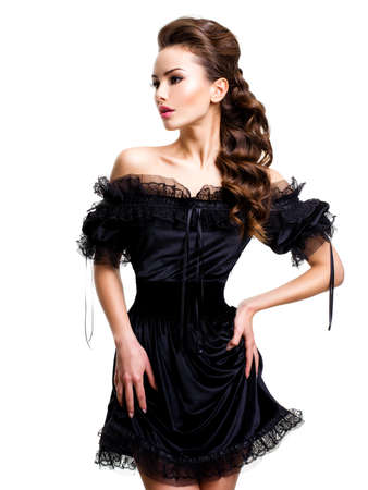 Jeune femme sexy posant robe noire au studio sur fond blanc Banque d'images