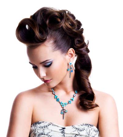 maquillaje de ojos: Retrato de perfil de una mujer joven hermosa con el peinado creativo y brillante maquillaje de ojos de color. Modelo de manera que el desgaste del pendiente azul y collar - aislados en blanco Foto de archivo